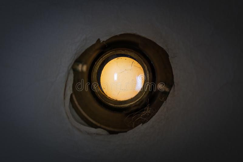 Peephole of the front door. Peephole of the dark front door of an old apartment royalty free stock images