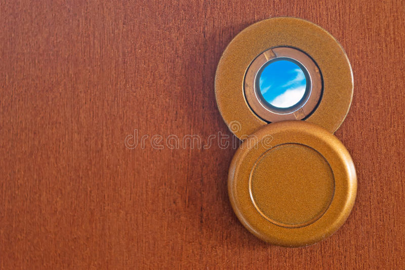 Peephole and sky. Peephole on a wooden door stock photography