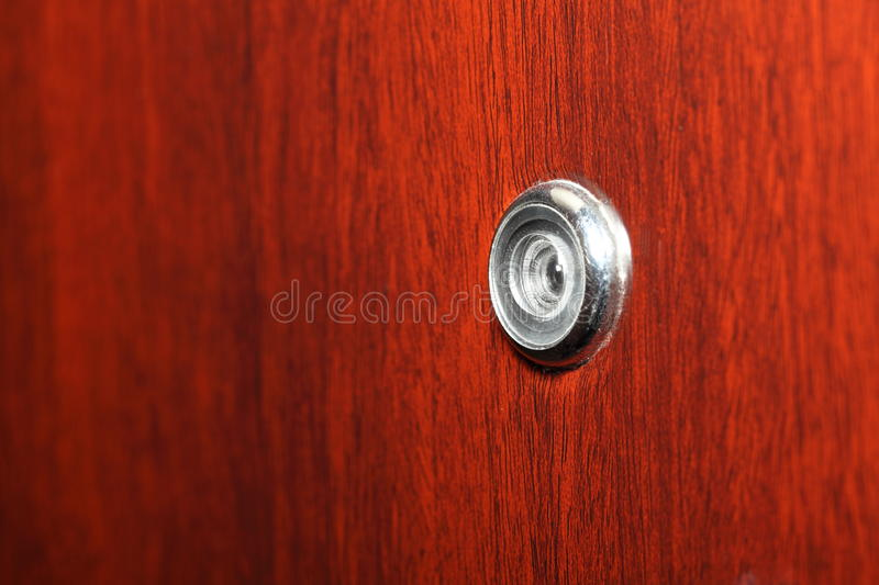 Peephole on wooden door. Judas hole spyhole stock image