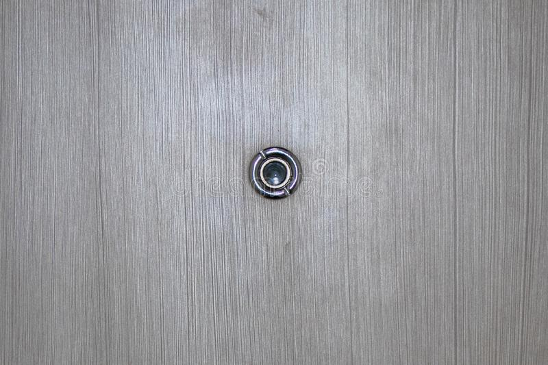 Peephole on wooden door. Close up door lens peephole on white wooden texture royalty free stock photos