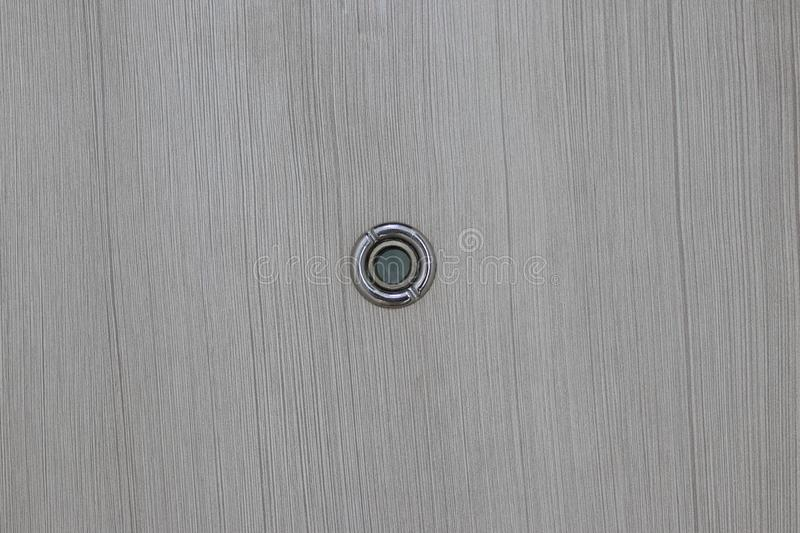Peephole on wooden door. Close up door lens peephole on white wooden texture stock image