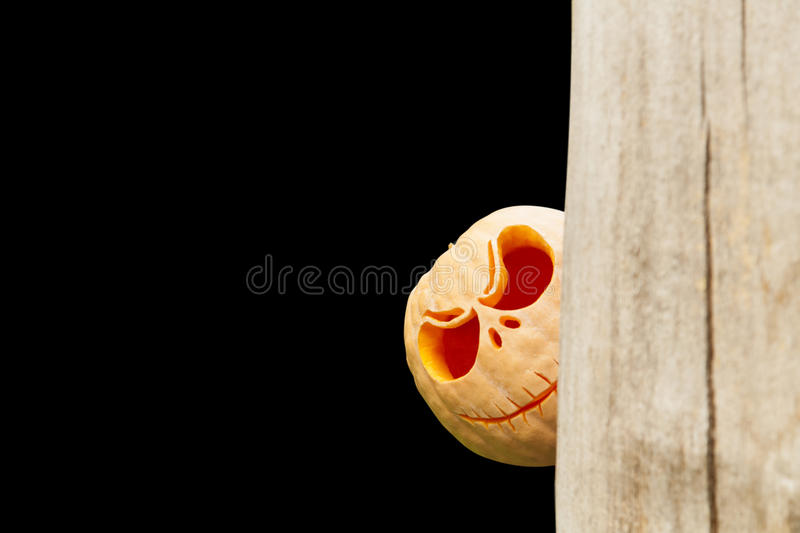 Peeping out halloween pumpkin on black royalty free stock images