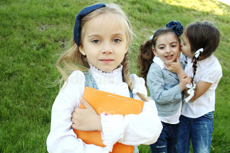 Peer pressure. Two little girls were whispering and laughing behind your back girlfriend. Girls 4-5 years. Good image for peer pressure royalty free stock photography