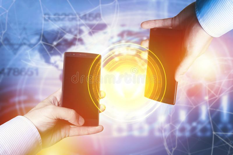 Peer-to-peer payment concept with map and world connection. Businessmen holding smartphones. Fintech concept stock photo