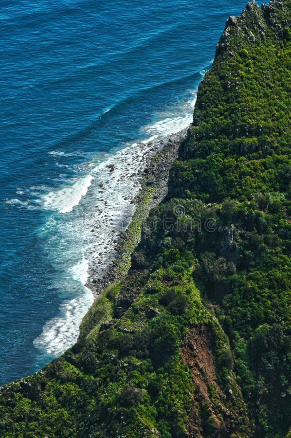 Peering over a cliff edge, ocean coastline. A precarious glance over a cliff edge looking down over cliffs, rocks and breaking waves in the ocean. On the island stock image