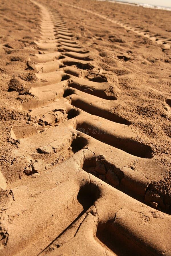 Pegada industrial do trator na areia da praia fotos de stock