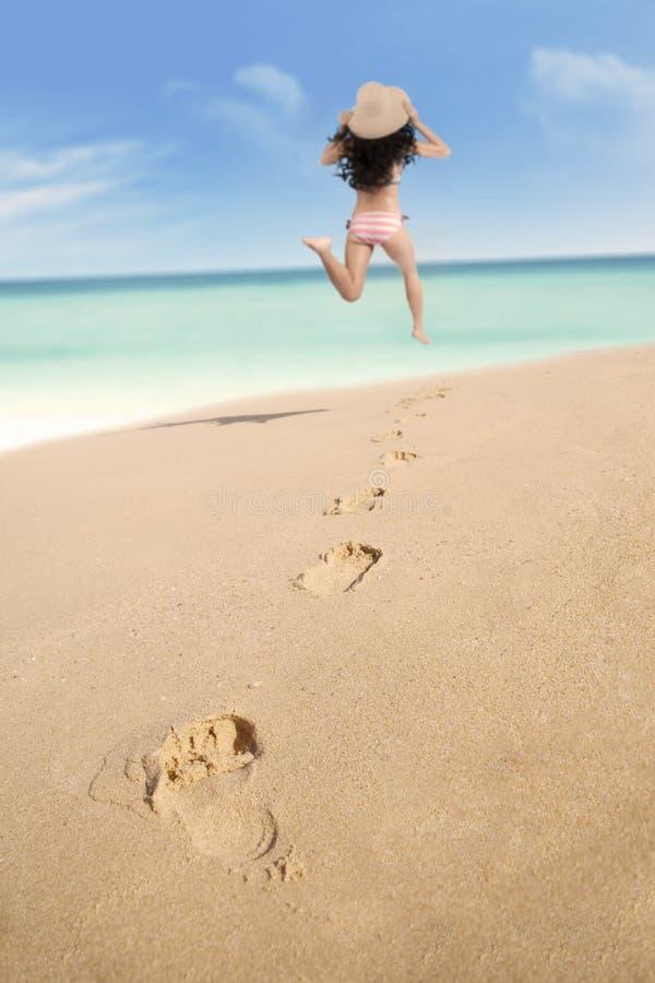 Pegadas e mulher entusiasmado que correm na praia foto de stock