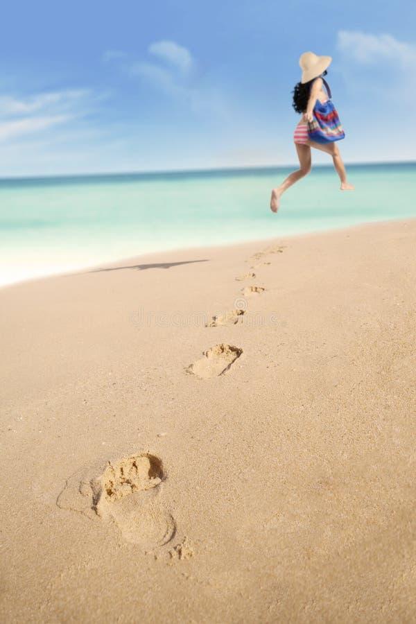 Pegadas e mulher que correm na praia fotografia de stock