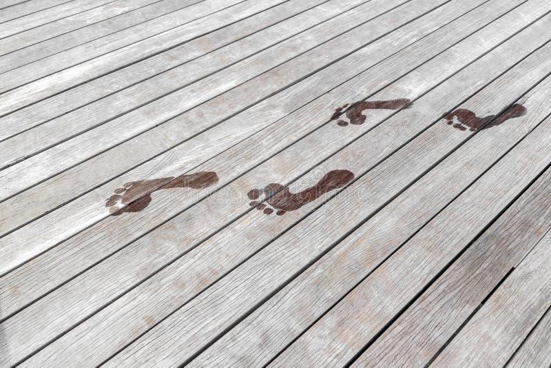 Pegadas molhadas em um terraço de madeira foto de stock