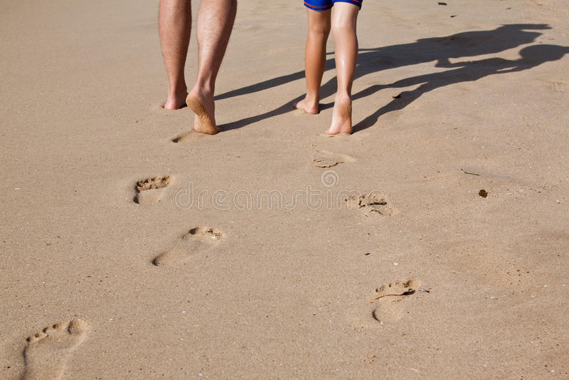 Pegadas na areia molhada do pai e do filho foto de stock