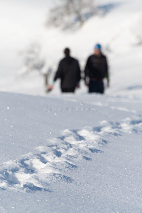 Pegadas na neve recentemente caída e dois nos caminhantes visíveis no fundo foto de stock