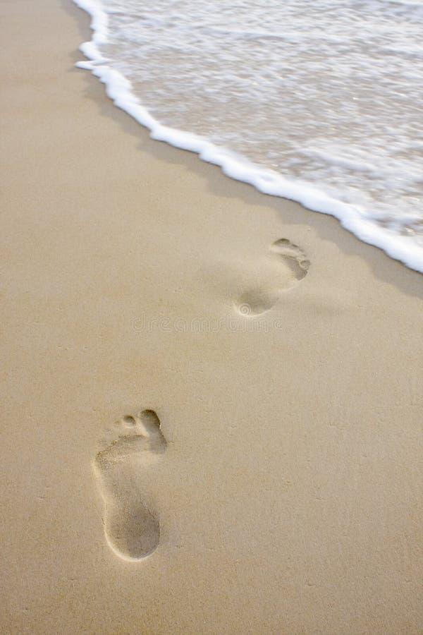 Pegadas na praia e na onda fotografia de stock