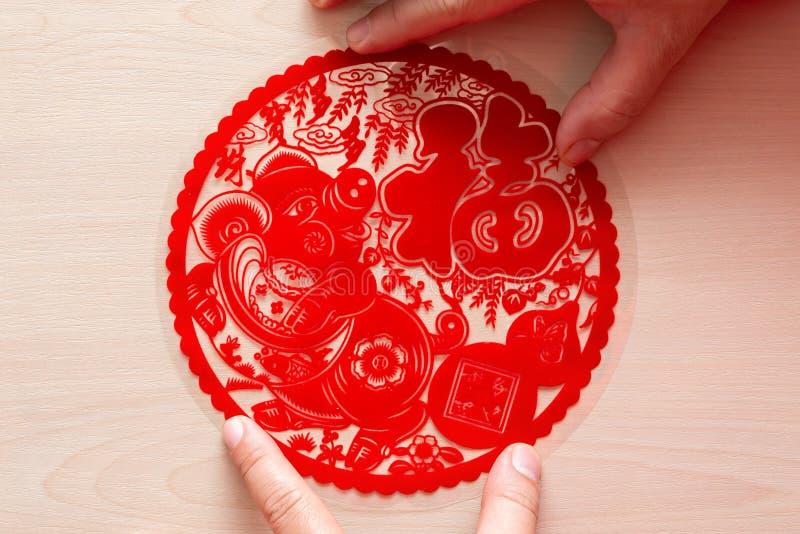 Pegando la etiqueta engomada plana roja mullida del papel-corte como símbolo del Año Nuevo chino del cerdo la buena suerte de los foto de archivo