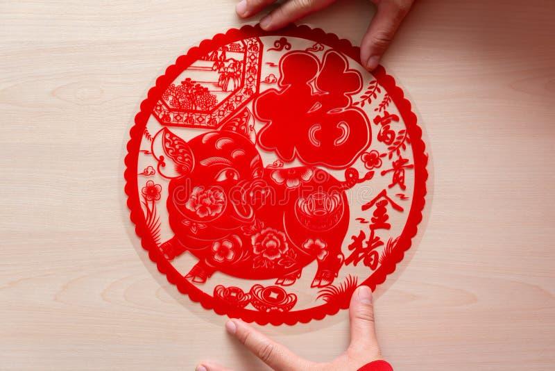 Pegando la etiqueta engomada plana roja mullida del papel-corte como símbolo del Año Nuevo chino del cerdo la buena suerte de los imagen de archivo libre de regalías
