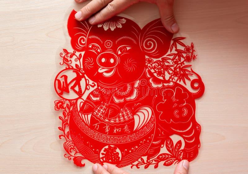 Pegando la etiqueta engomada plana roja mullida del papel-corte como símbolo del Año Nuevo chino del cerdo los medios chinos todo fotografía de archivo libre de regalías