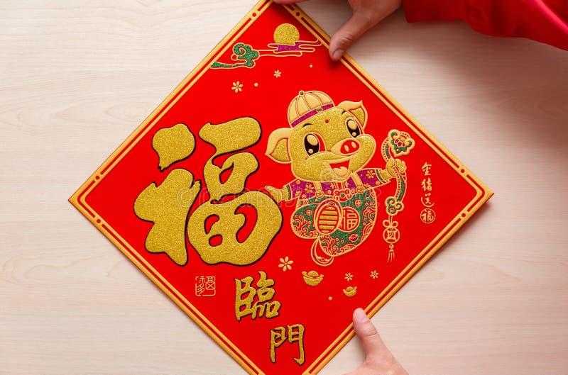 Pegando la etiqueta engomada roja mullida como símbolo del Año Nuevo chino del cerdo los medios chinos el cerdo le traen fortuna  imágenes de archivo libres de regalías