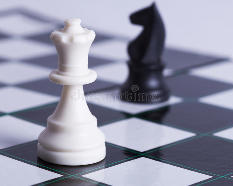 Pegno bianco e cavaliere nero sulla scacchiera immagine stock