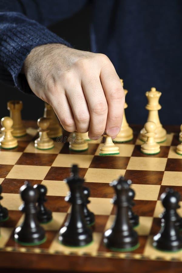 Pegno commovente della mano sulla scheda di scacchi fotografia stock libera da diritti