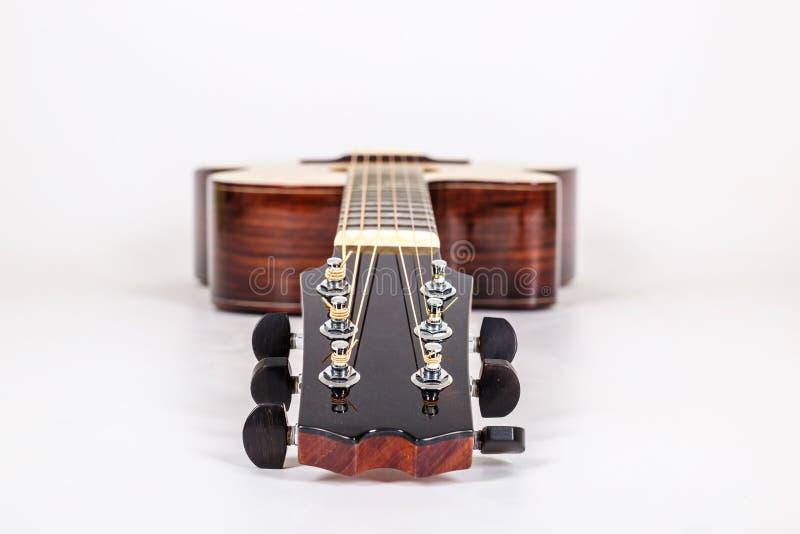 Pegs de ajustamento em uma cabeça de madeira da máquina de seis guitarra das cordas no fundo branco foto de stock