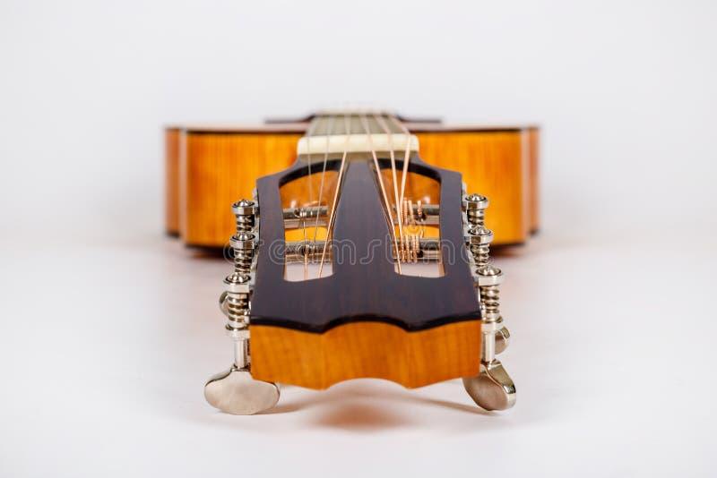 Pegs de ajustamento em uma cabeça de madeira da máquina de seis guitarra das cordas no fundo branco fotografia de stock
