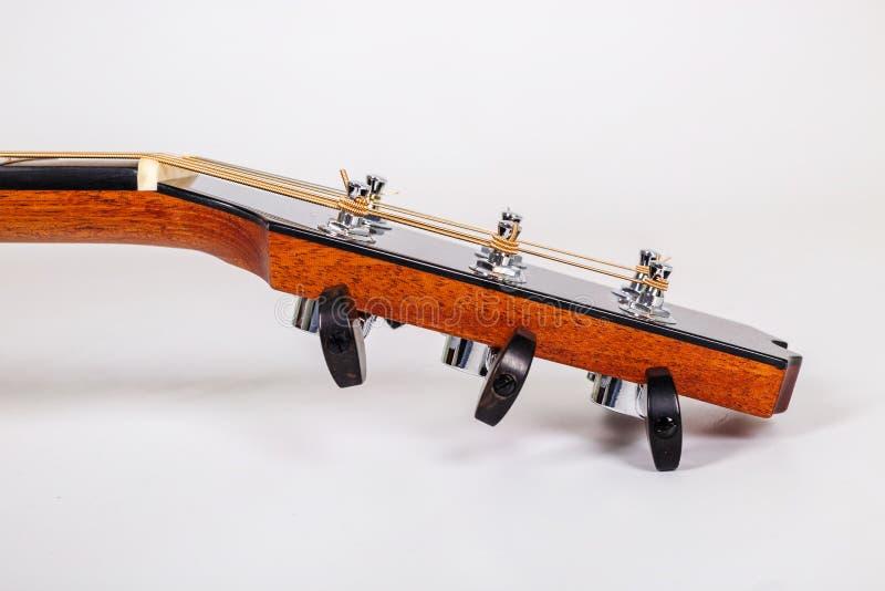 Pegs de ajustamento em uma cabeça de madeira da máquina de seis guitarra das cordas no fundo branco fotos de stock royalty free