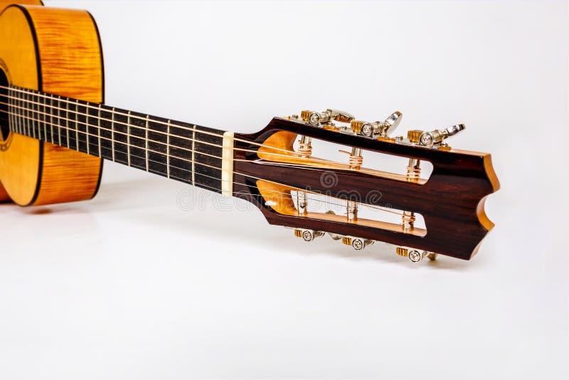 Pegs de ajustamento em uma cabeça de madeira da máquina de seis guitarra das cordas no fundo branco imagens de stock