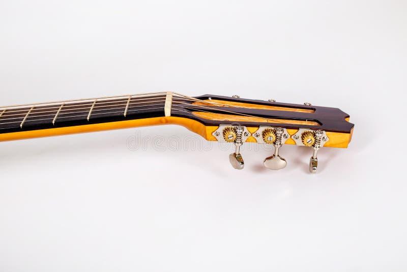 Pegs de ajustamento em uma cabeça de madeira da máquina de seis guitarra das cordas no fundo branco imagens de stock royalty free