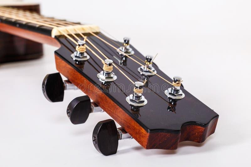 Pegs de ajustamento em uma cabeça de madeira da máquina de seis guitarra das cordas no fundo branco fotos de stock