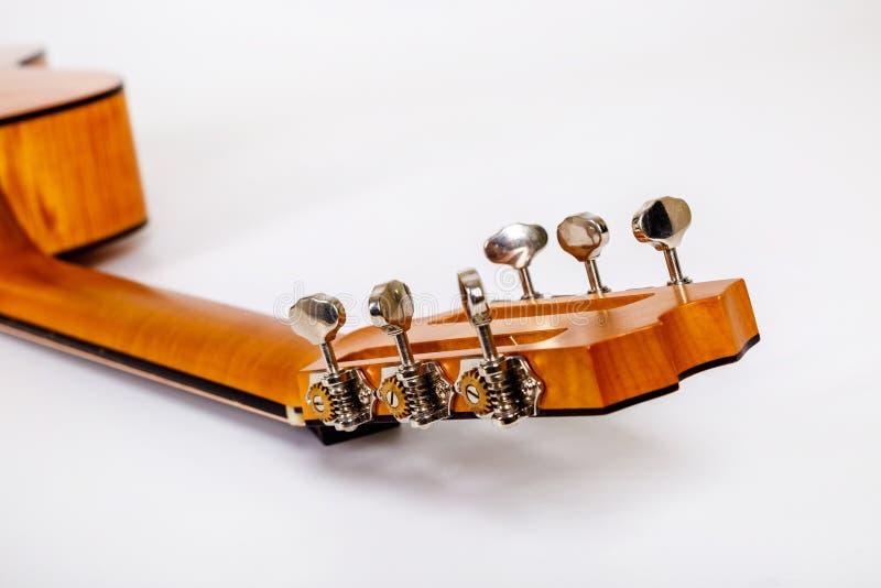 Pegs de ajustamento em uma cabeça de madeira da máquina de seis guitarra das cordas no fundo branco imagem de stock
