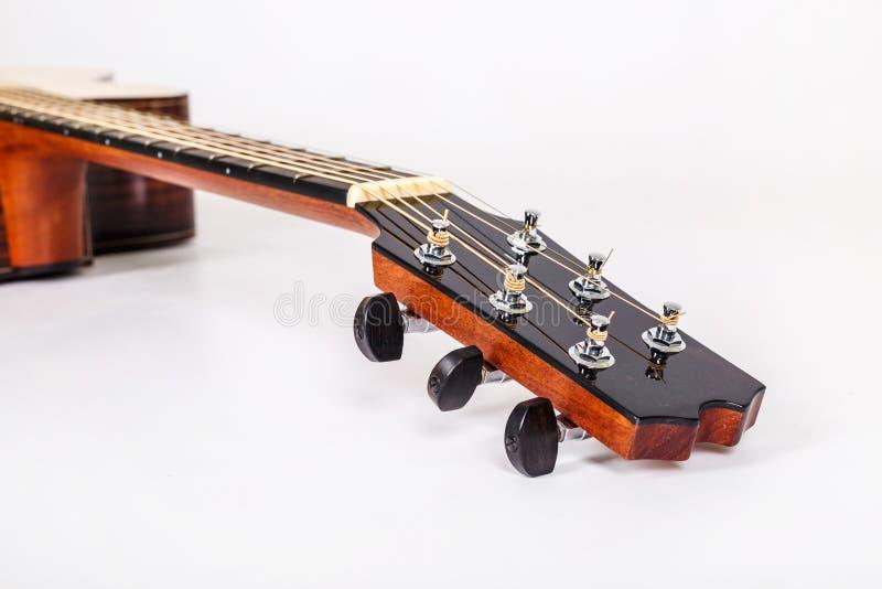 Pegs de ajustamento em uma cabeça de madeira da máquina de seis guitarra das cordas no fundo branco imagem de stock royalty free