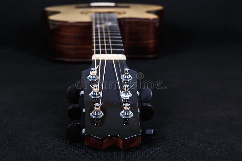Pegs de ajustamento em uma cabeça de madeira da máquina de seis pescoços da guitarra acústica das cordas no fundo preto fotos de stock royalty free