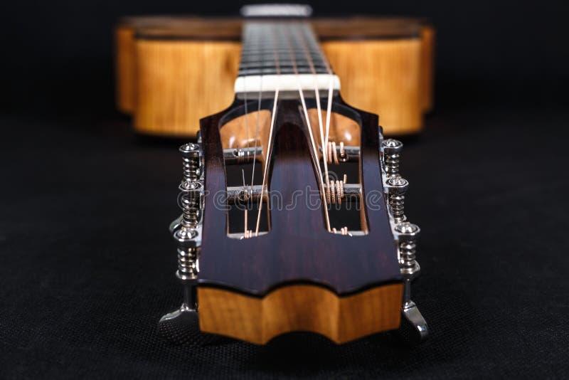 Pegs de ajustamento em uma cabeça de madeira da máquina de seis pescoços da guitarra acústica das cordas no fundo preto fotografia de stock