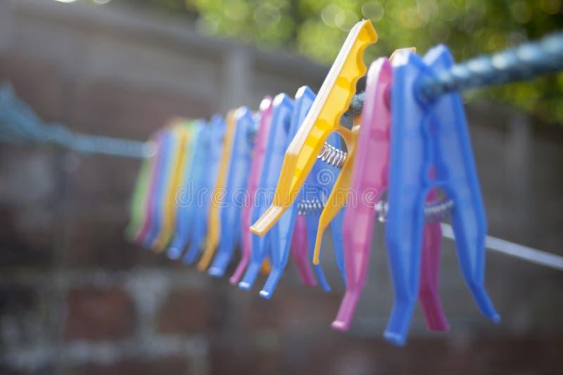 Pegs de roupa plásticos que colocam no fio foto de stock