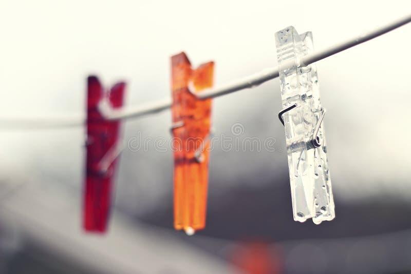 Pegs de roupa que penduram fora na chuva do verão Pegs vermelhos, alaranjados e transparentes imagem de stock