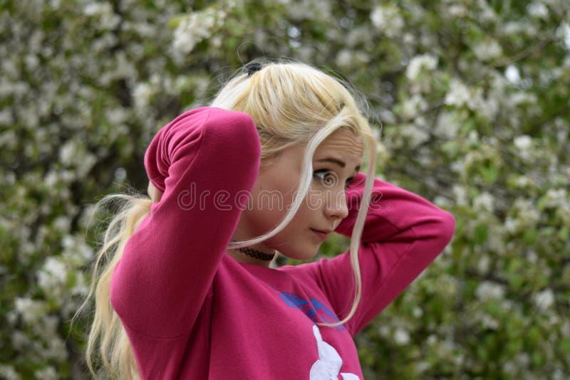 Peignée de la queue de la longue jeune fille de cheveux blonds sur le fond d'un pommier de floraison photographie stock libre de droits