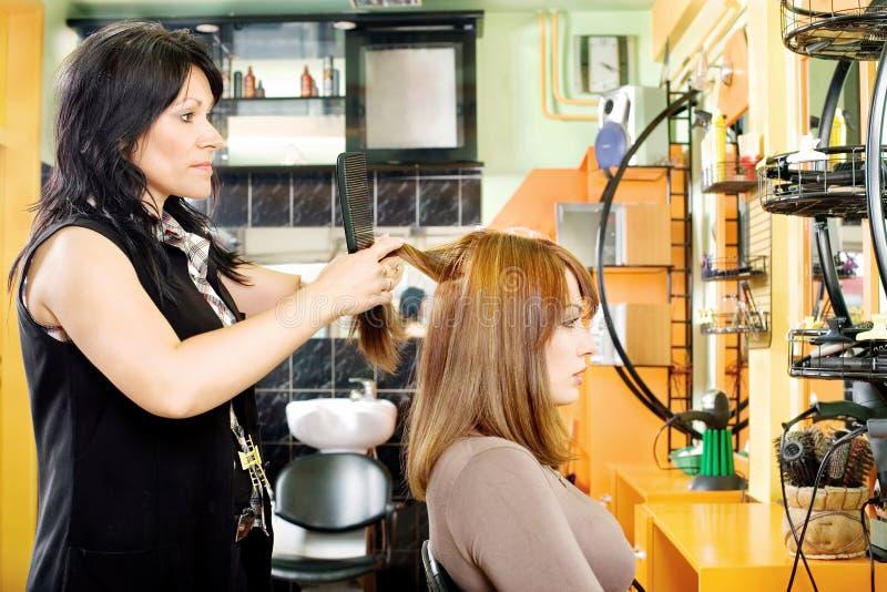 Peignée des cheveux du client photographie stock