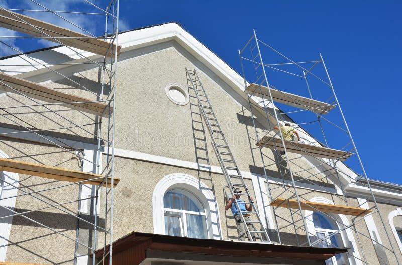 Peignant et plâtrant le mur extérieur d'échafaudage de Chambre L'isolation thermique et le stuc de façade fonctionne pendant des  images libres de droits