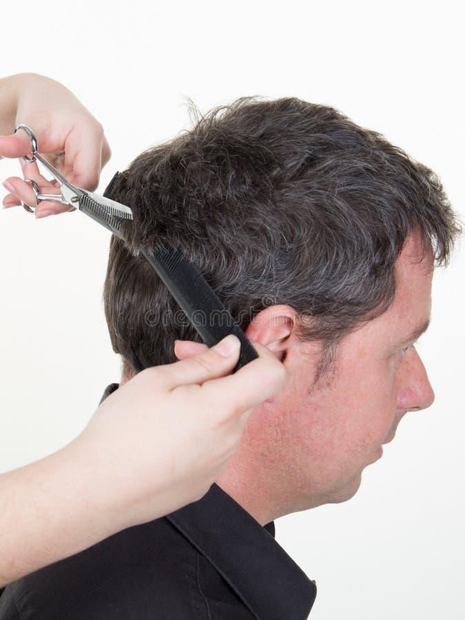Peigne et ciseaux de participation de coiffeur chez l'homme bel avec les cheveux noirs ayant la coupe de cheveux au-dessus du fon images libres de droits
