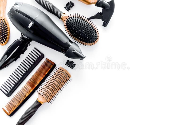 Peignes et outils de coiffeur dans le salon de beauté sur le copyspace blanc de vue supérieure de fond photographie stock libre de droits