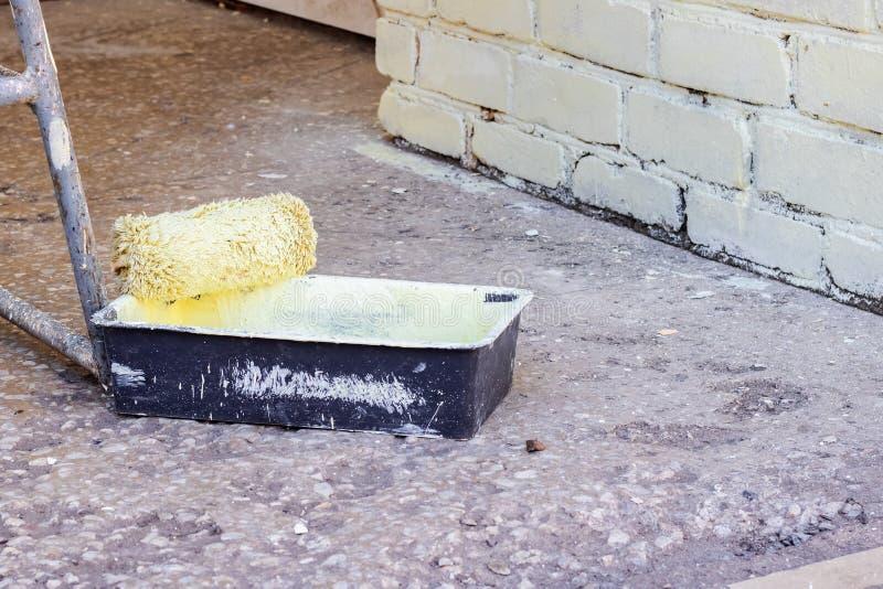 Peignez le rouleau et le conteneur avec la peinture jaune image libre de droits