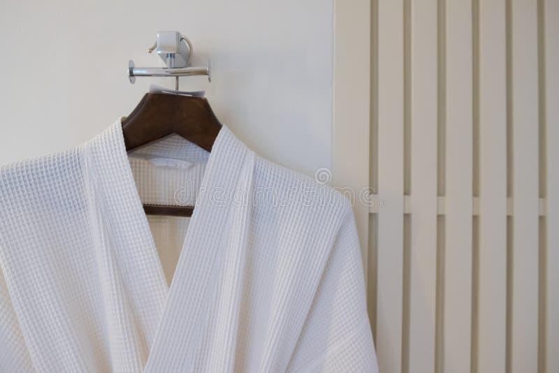 Peignoir blanc sur un cintre sur le mur photos stock