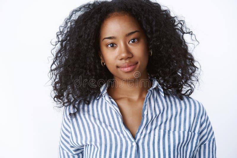 Peinado afro de amistoso-mirada encantador esperanzado sincero del estudiante universitario joven de piel morena del primer que i imagen de archivo libre de regalías