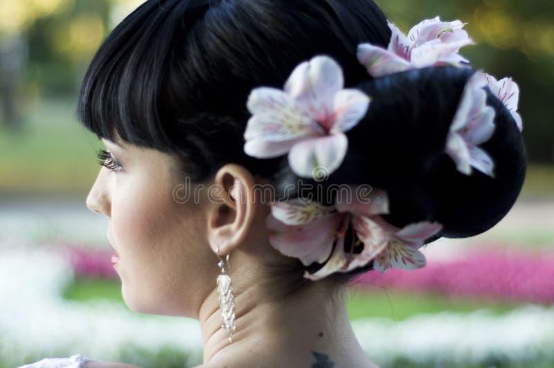 Peinado de la boda en el pelo negro con las flores foto de archivo libre de regalías