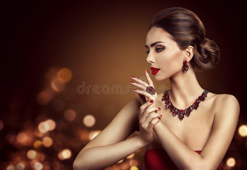 Peinado del bollo del pelo de la mujer, joyería de Beauty Makeup Red del modelo de moda fotografía de archivo