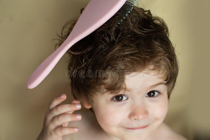 Peinado para un niño Beb? con un peine Muchacho elegante Peinar el pelo barbershop Sal?n de la belleza Niño lindo con el pelo moj fotografía de archivo libre de regalías