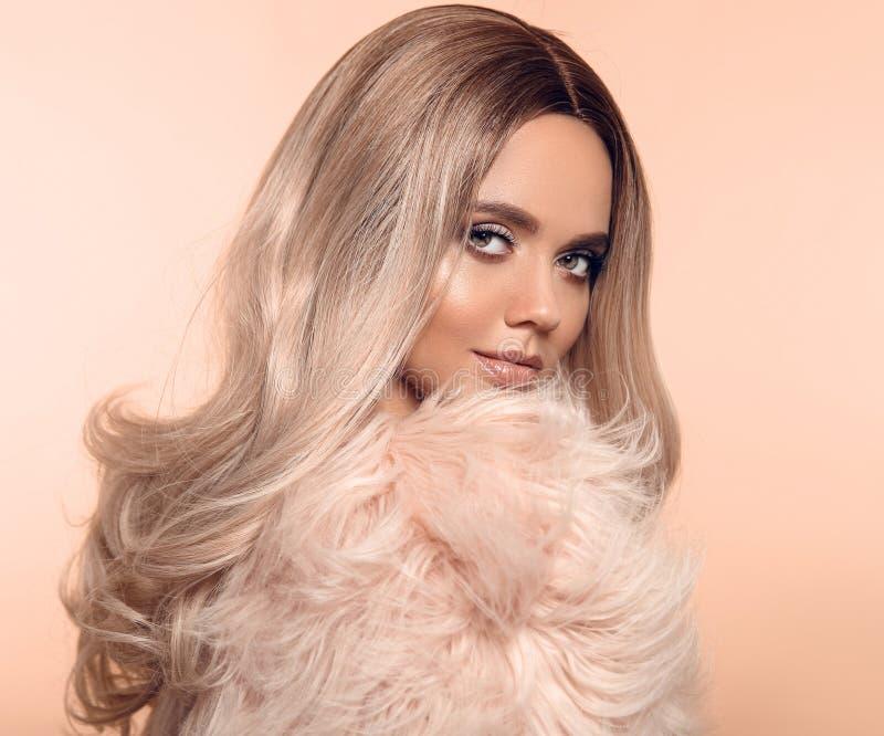 Peinado rubio de Ombre Retrato rubio de la moda de la belleza La mujer atractiva lleva en abrigo de pieles rosado Modelo hermoso  imagen de archivo