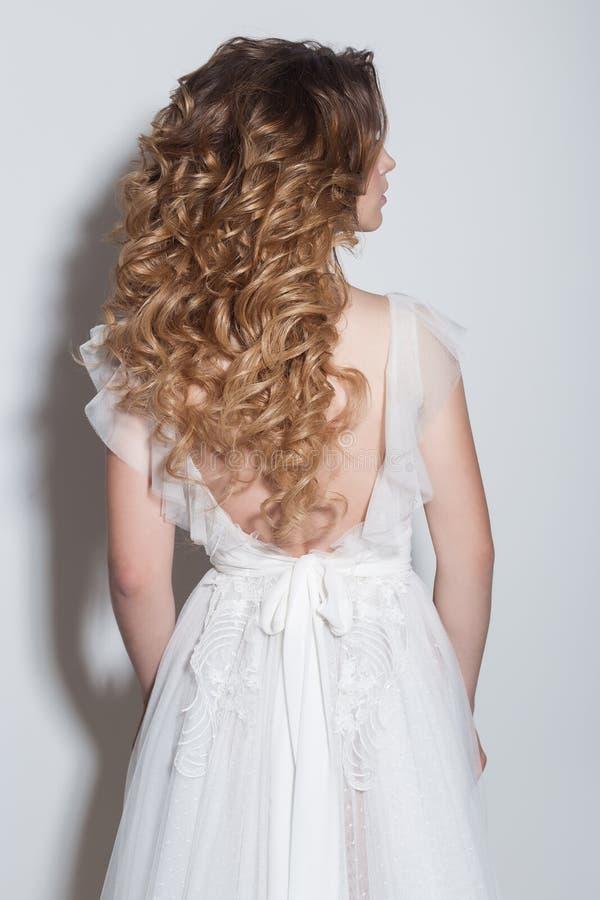 Peinados de moda hermosos para la novia delicada hermosa de las chicas jóvenes en un vestido de boda hermoso en un fondo blanco e imagenes de archivo