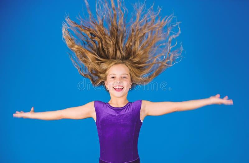 Peinados latinos de la danza del salón de baile Muchacha del niño con el vestido largo del desgaste del pelo en fondo azul Peinad imagenes de archivo