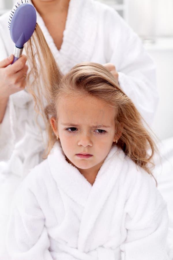 Peinando y tirando del pelo - el precio de la belleza foto de archivo libre de regalías