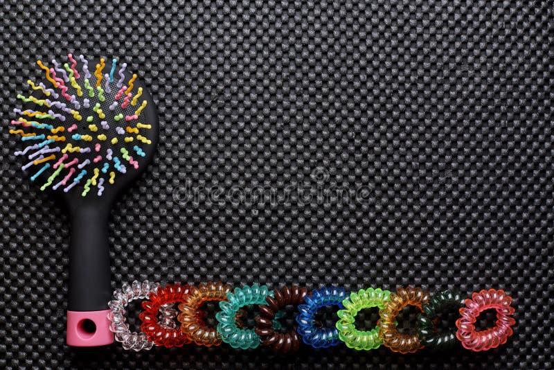 Peine multicolor brillante y una fila de gomas coloreadas en un fondo negro fotografía de archivo libre de regalías